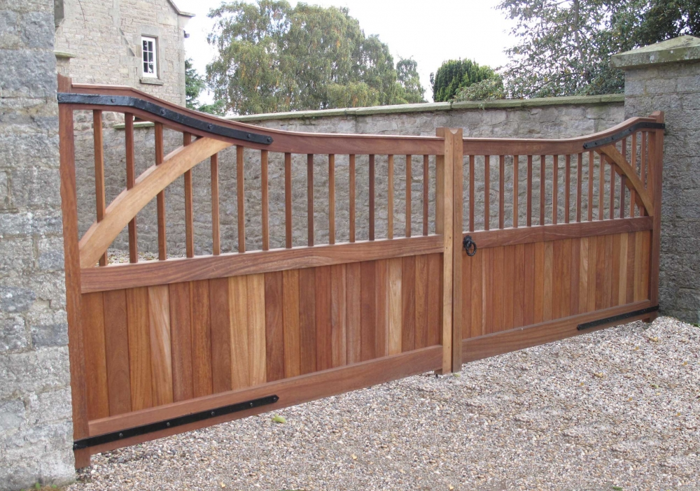 Hardwood gates in iroko Leighton style with curved top, semi boarded with uprights and curved braces