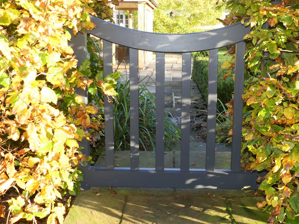 Small modern wooden garden gate that you can see through with curved top and plain uprights