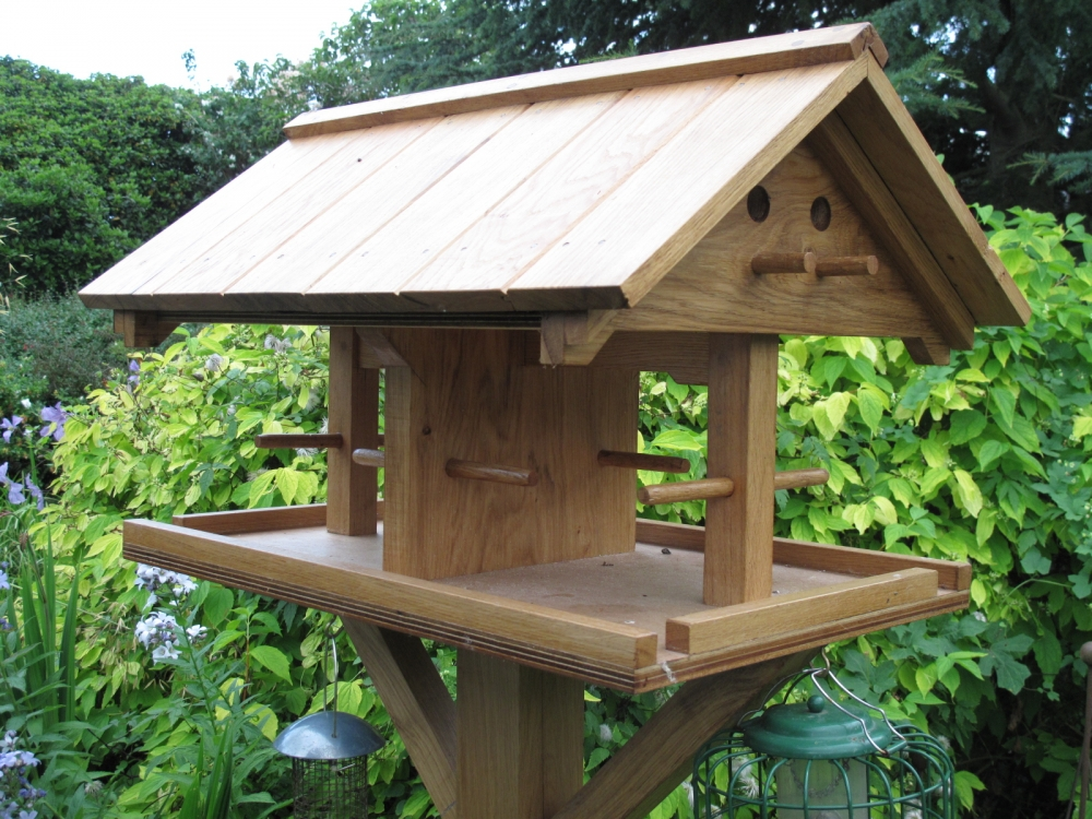 Oak or iroko hardwood bird table with hinged lid and perch rests